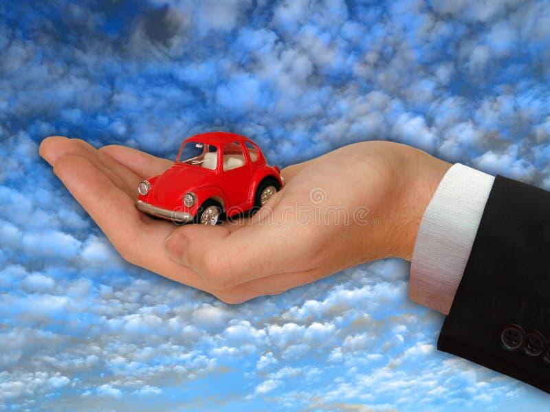Mão do homem de negócios com o carro vermelho encantador fotos de stock