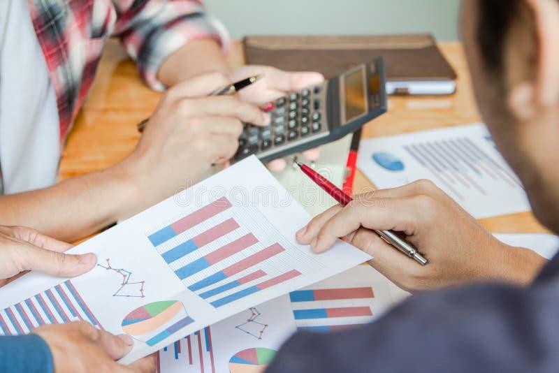 Mão do homem de negócios do grupo usando a calculadora que calcula o bonusOr a outra compensação aos empregados para aumentar a p imagem de stock royalty free