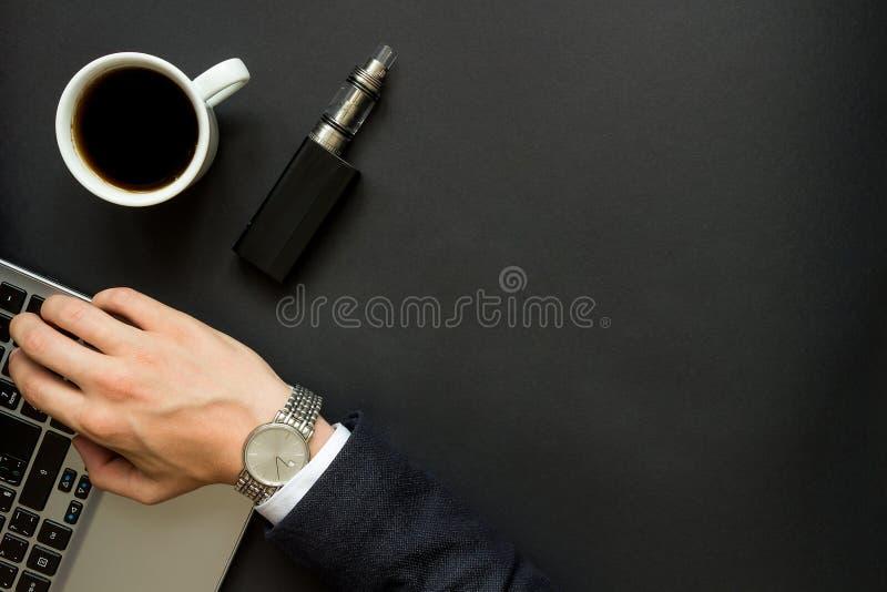 A mão do homem de negócios no portátil e no cigarro eletrônico imagem de stock