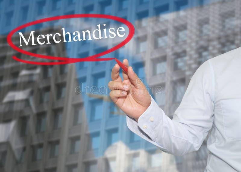 A mão do homem de negócios novo escreve a mercadoria da palavra no skyscrap fotos de stock