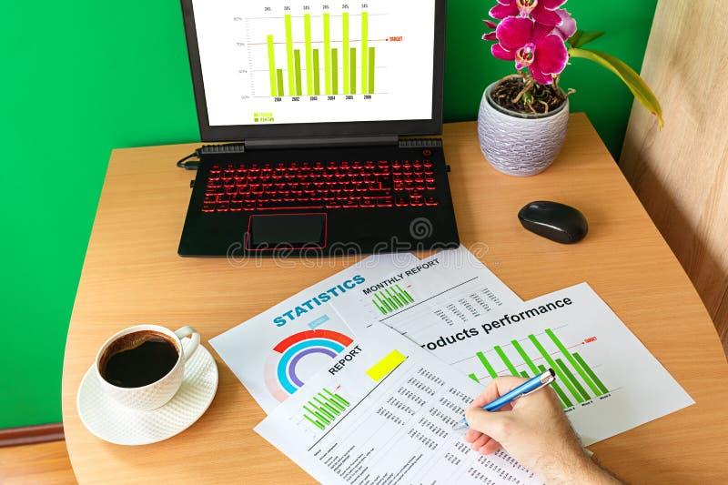 Mão do homem de negócios que analisa gráficos e cartas financeiros de negócio do relatório imagens de stock
