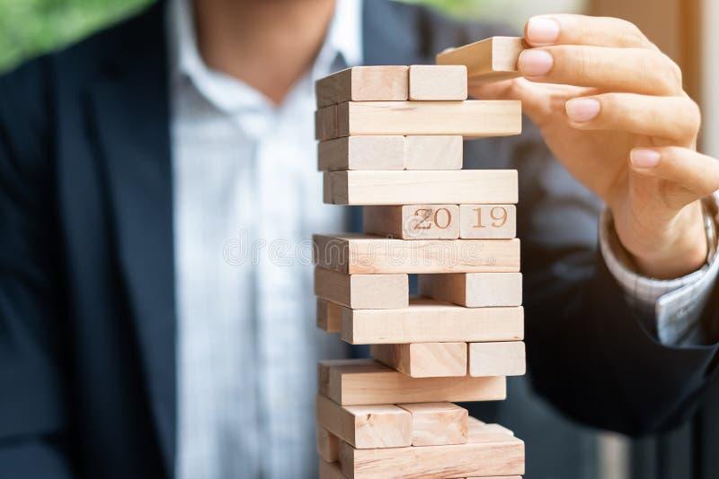 Mão do homem de negócios que coloca ou que puxa o bloco de madeira na torre Planeamento empresarial, gestão de riscos fotografia de stock royalty free