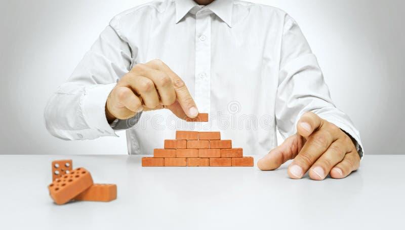 Mão do homem de negócios que coloca um tijolo em uma parede fotografia de stock