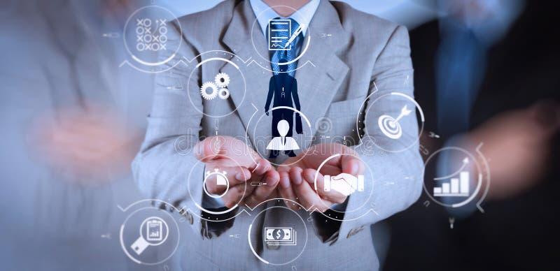 Mão do homem de negócios que escolhe o ícone dos povos como o conceito dos recursos humanos foto de stock
