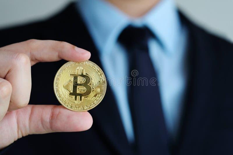 Mão do homem de negócios que guarda bitcoins, cryptocurrency e blockchain fotos de stock royalty free