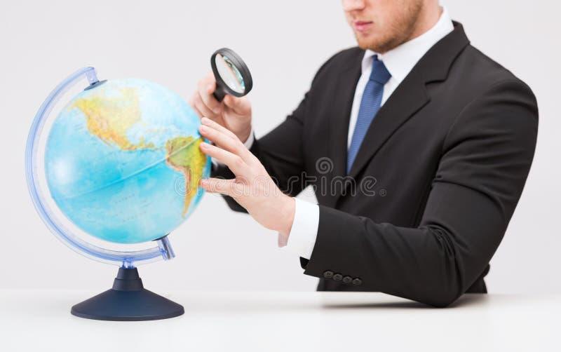 Mão do homem de negócios que guarda a lente de aumento sobre o globo imagens de stock
