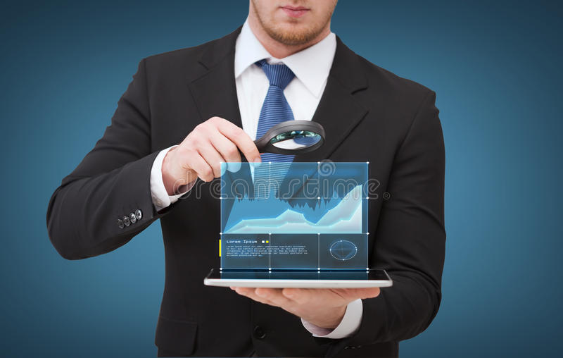 Mão do homem de negócios que guarda a lente de aumento sobre o PC da tabuleta fotos de stock royalty free