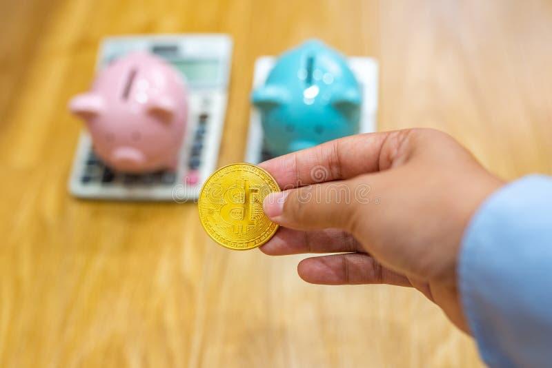 Mão do homem de negócios que guarda o bitcoin com piggybank e calculadora atrás imagem de stock
