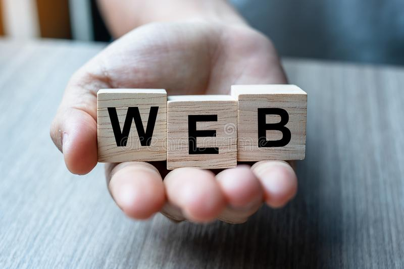 Mão do homem de negócios que guarda o bloco de madeira do cubo com palavra do negócio da WEB no fundo da tabela Web site, rede, b fotografia de stock