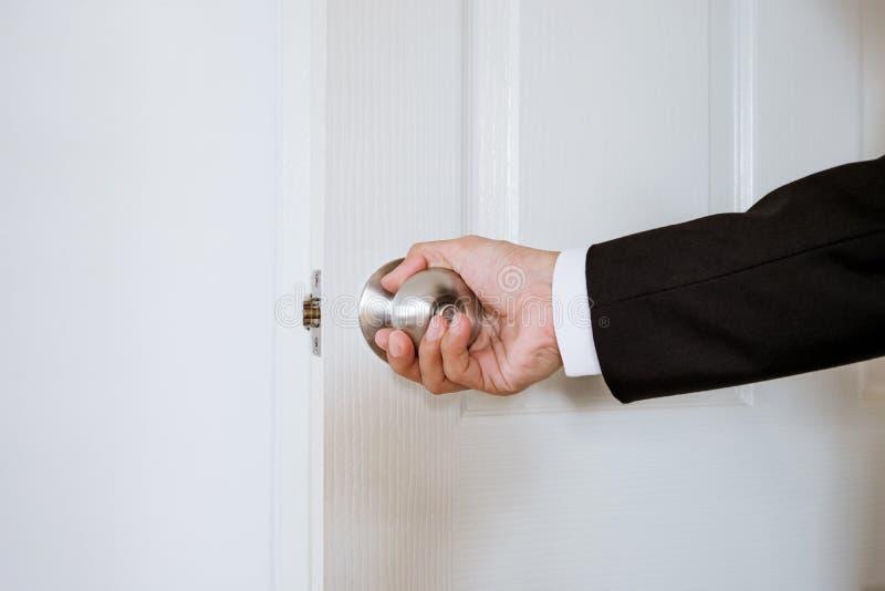 Mão do homem de negócios que guarda o botão de porta, abertura ou fechando a porta, com o brilhante atrás da porta fotografia de stock royalty free