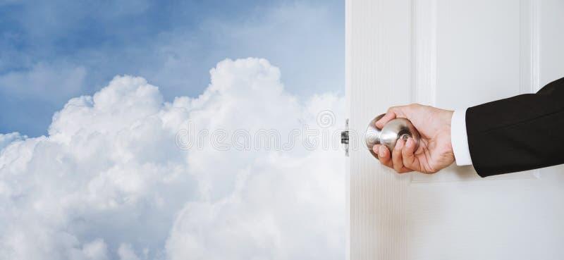 Mão do homem de negócios que guarda o botão de porta, abrindo ao céu e às nuvens, com espaço da cópia, conceito abstrato do negóc fotografia de stock royalty free