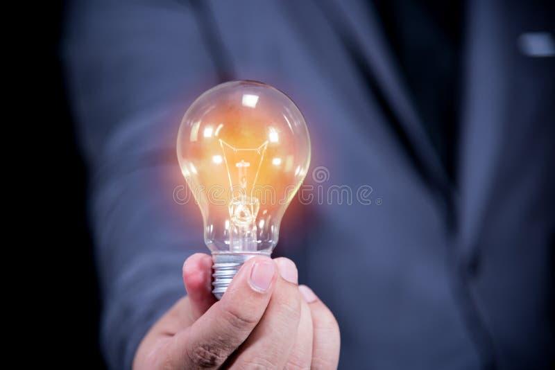 Mão do homem de negócios que guarda o concep da ampola, da ideia e da tecnologia foto de stock royalty free