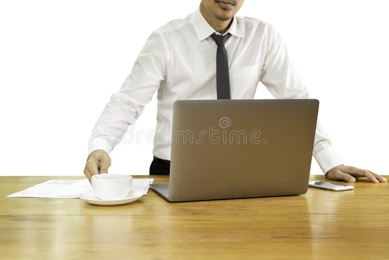 Mão do homem de negócios que guarda o copo de café com o portátil na mesa de madeira no trajeto de grampeamento fotografia de stock