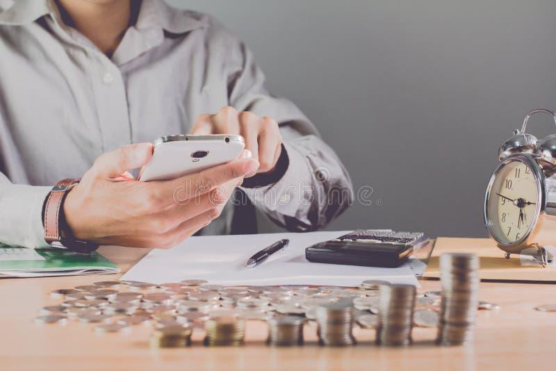 Mão do homem de negócios que guarda o telefone celular na tabela com uma medalha que reconhece a computação e Fundo claro do negó foto de stock royalty free