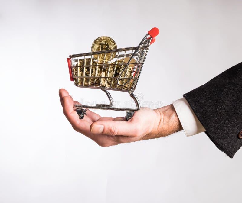 Mão do homem de negócios que guarda um carrinho de compras fotografia de stock