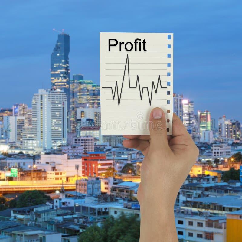 Mão do homem de negócios que guarda uma nota de papel com lucro e lin imagens de stock