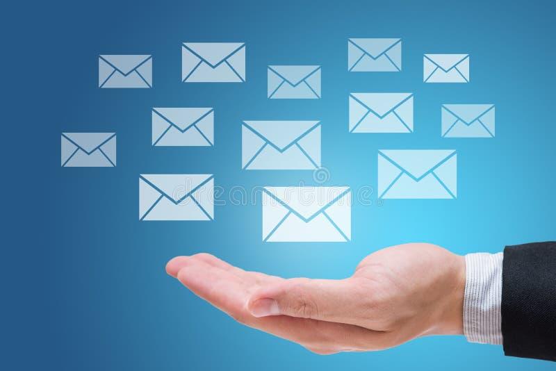 Mão do homem de negócios que guardam mensagens ou letra isolada no fundo azul imagens de stock