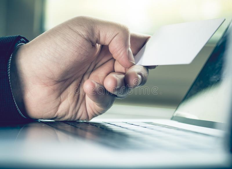 A mão do homem de negócios que guardam o cartão de crédito e o vintage do portátil do uso tonificam fotos de stock royalty free