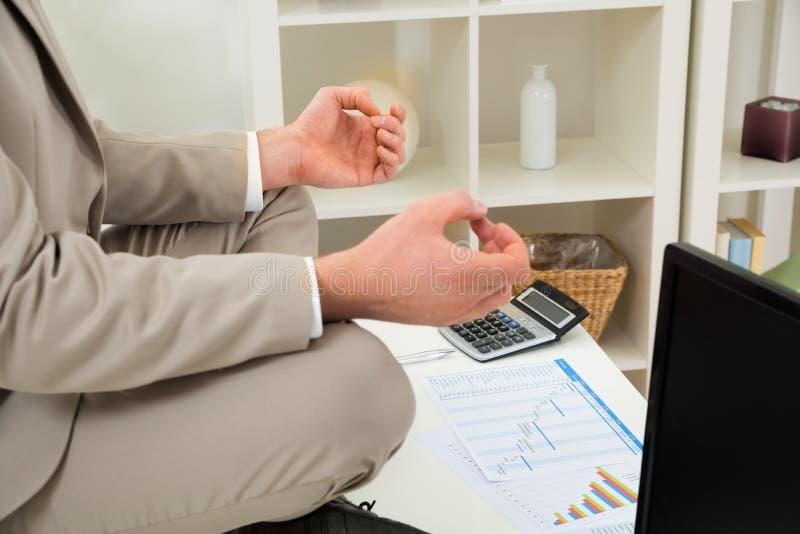 Mão do homem de negócios que medita no local de trabalho fotografia de stock