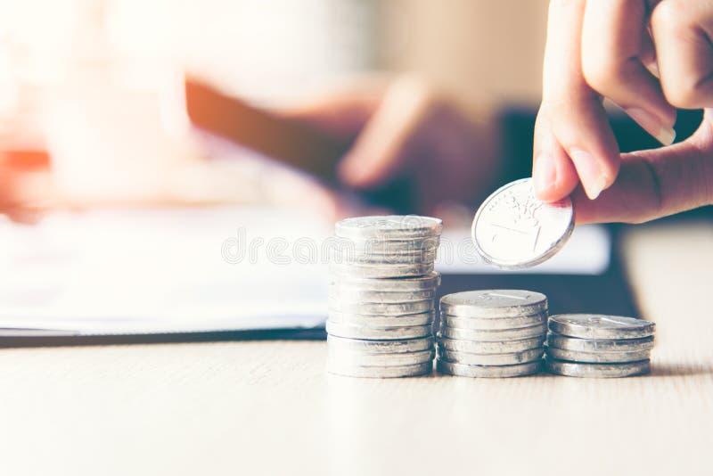 Mão do homem de negócios que põe a pilha de planta crescente da tampa do dinheiro da moeda para o relatório financeiro do investi imagens de stock