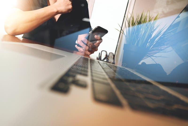 Mão do homem de negócios usando o telefone celular com o laptop como o busi imagens de stock
