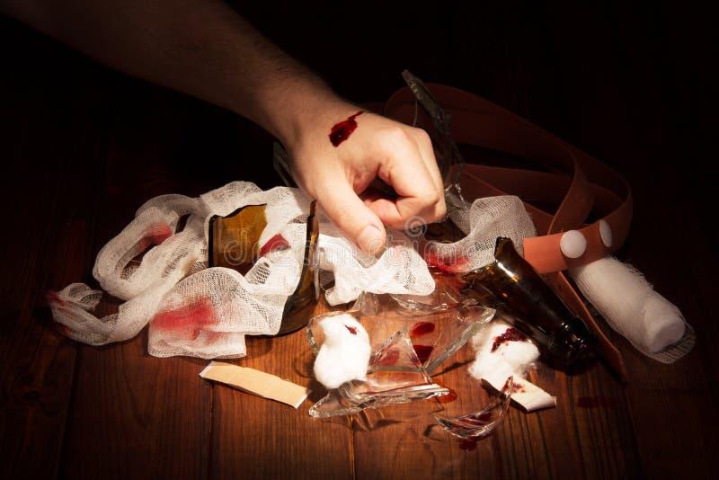 A mão do homem desbastou o vidro e os meios parar de sangrar na madeira escura foto de stock