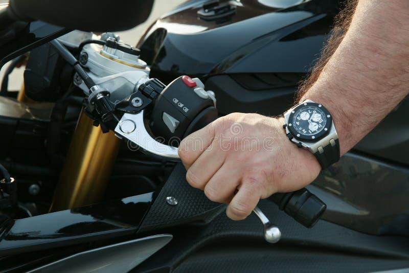 A mão do homem desligou a embreagem em um fim da motocicleta acima foto de stock