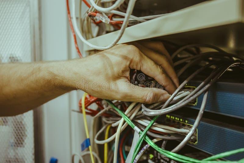 A mão do homem do coordenador conecta o cabo da rede ao interruptor do cubo da fibra ótica para comunicações digitais na sala do  fotografia de stock royalty free