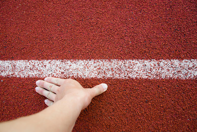 Mão do homem do corredor da vista superior nas linhas brancas da trilha de posição de começo que correm no estádio do esporte imagens de stock royalty free