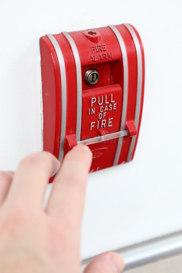 A mão do homem está puxando o alarme de incêndio imagens de stock