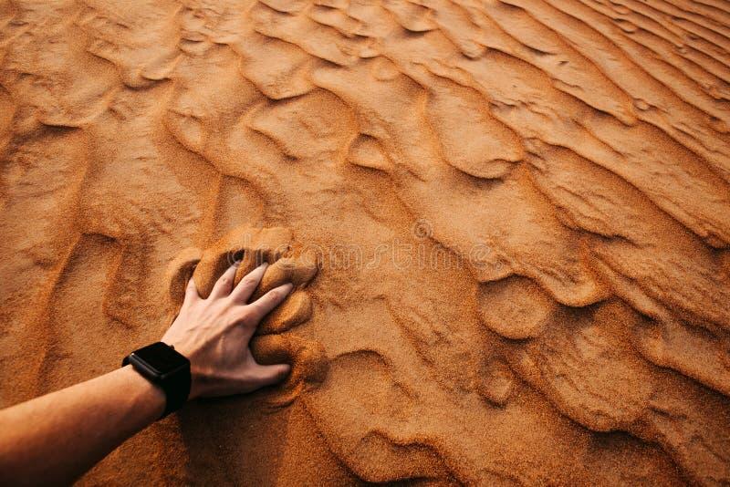 A mão do homem está tocando na areia no deserto foto de stock royalty free