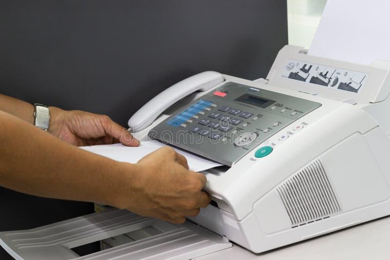 A mão do homem está usando um fax no escritório imagens de stock royalty free
