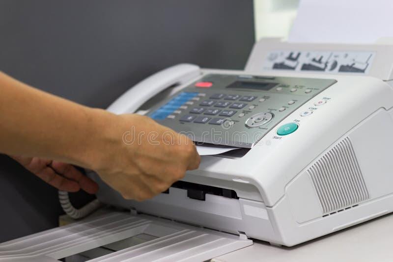 A mão do homem está usando um fax no escritório fotografia de stock royalty free