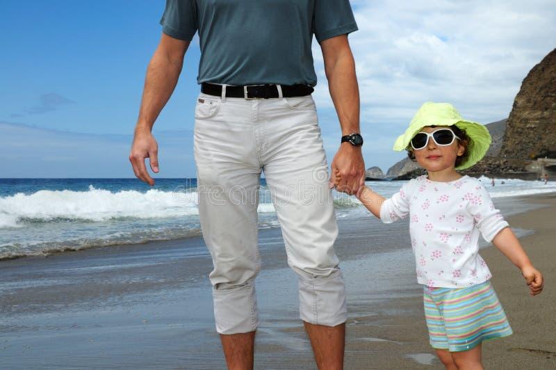 Mão do homem feliz da terra arrendada da menina em uma praia fotos de stock royalty free