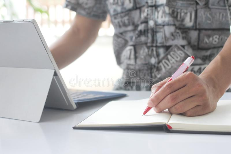 A mão do homem guarda a pena em um caderno vazio e em um caderno fotografia de stock royalty free