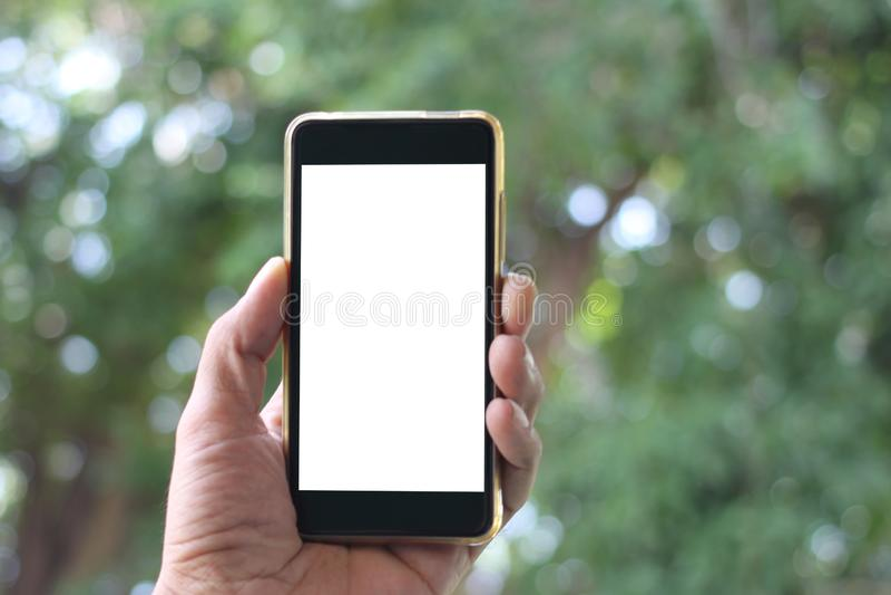 A mão do homem guarda a tela branca vazia do smartphon e tem a bobina foto de stock