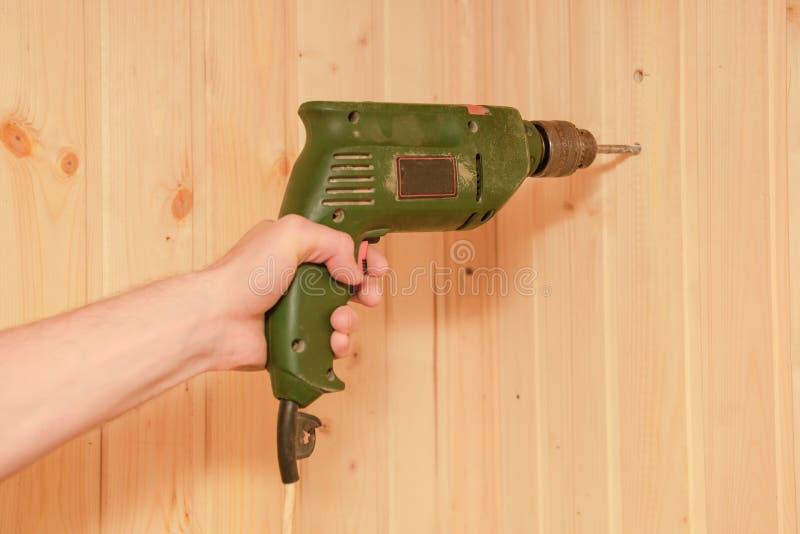 A mão do homem guarda uma broca elétrica velha e fura uma parede de madeira fotos de stock royalty free