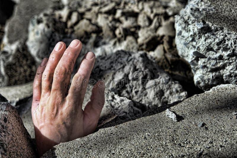 Mão do homem inoperante na entulho do concreto do terremoto imagem de stock
