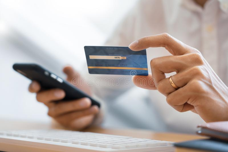 Mão do homem na camisa ocasional que paga com cartão de crédito e que usa o telefone esperto para a compra em linha que faz orden fotografia de stock royalty free