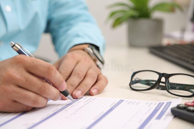 Mão do homem no formulário com pena Imagem do potenciômetro, do teclado e dos vidros de flor fotografia de stock