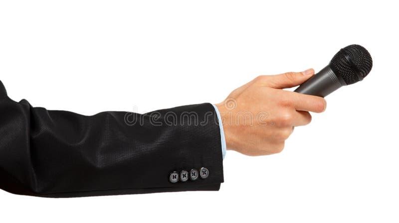 A mão do homem no terno preto que guarda um microfone imagens de stock