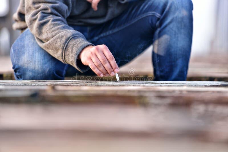 Mão do homem novo que extingue o cigarro em uma ponte velha con foto de stock