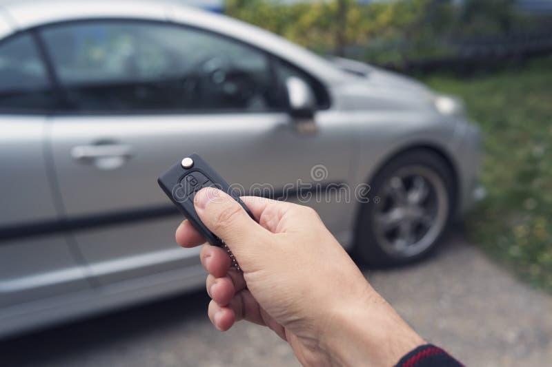 A mão do homem pressiona um botão no controlo a distância do carro contra o carro do borrão O novo proprietário de um veículo des foto de stock royalty free