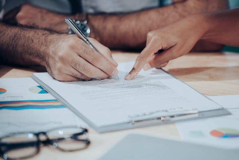 Mão do homem que assina um contrato no documento para a casa de construção econômica com arquiteto e sócio imagens de stock