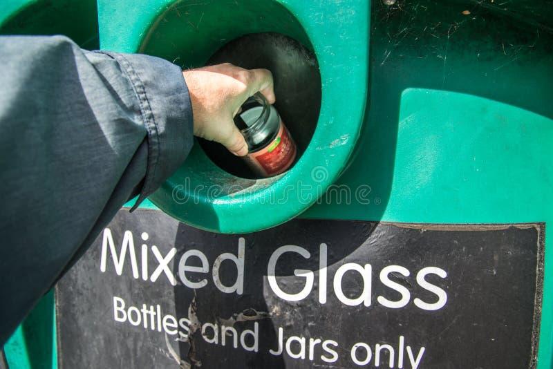 A mão do homem que coloca o frasco de vidro na reciclagem no banco da garrafa em U K imagem de stock royalty free