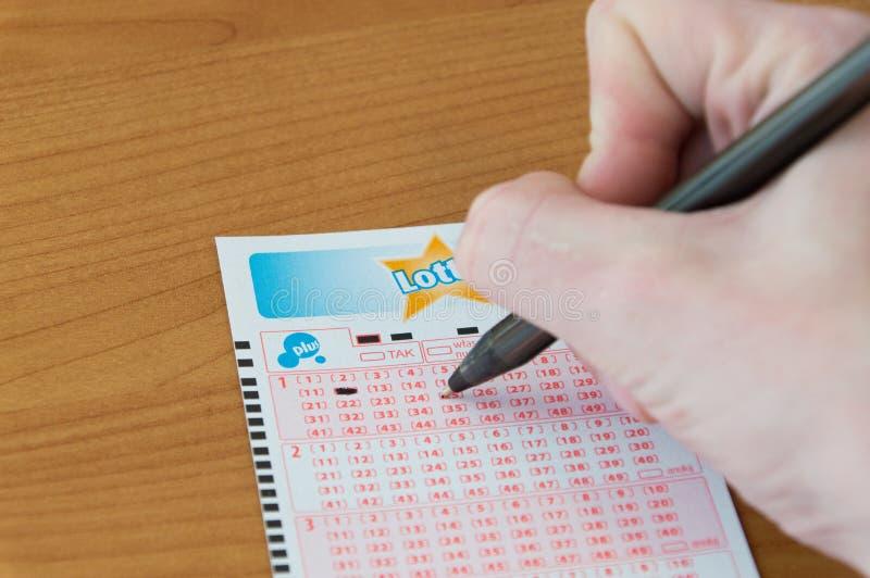 Mão do homem que completa um bilhete de loto O loto é loteria polonesa fotografia de stock