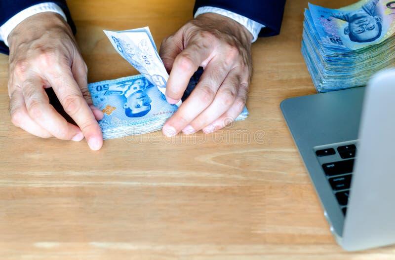 A mão do homem que conta o dinheiro tailandês novo cédula de 50 bahts fotografia de stock
