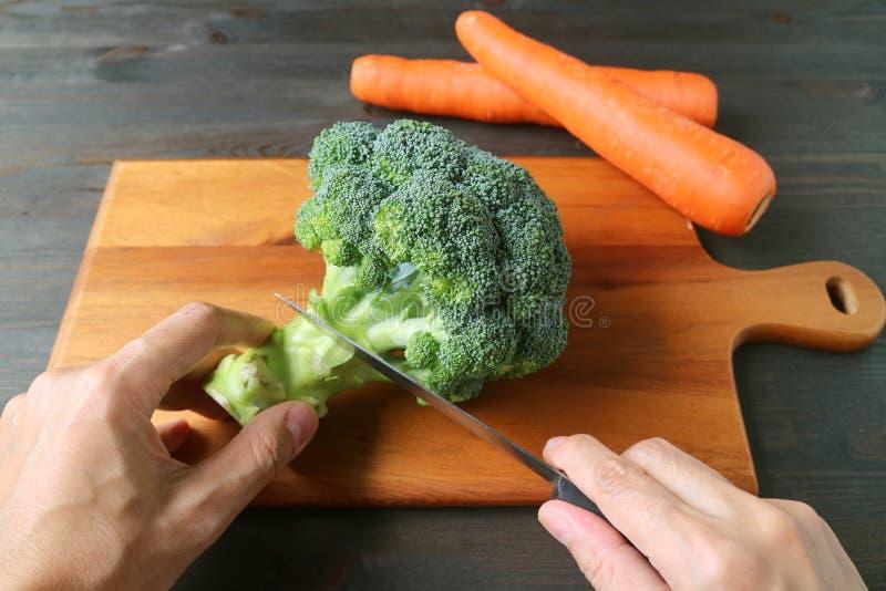 A mão do homem que corta brócolis na placa de corte de madeira com as cenouras obscuras no fundo fotos de stock