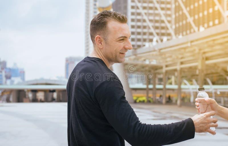 Mão do homem que dá a garrafa da água potável após ter corrido o exercício no capital fotos de stock royalty free
