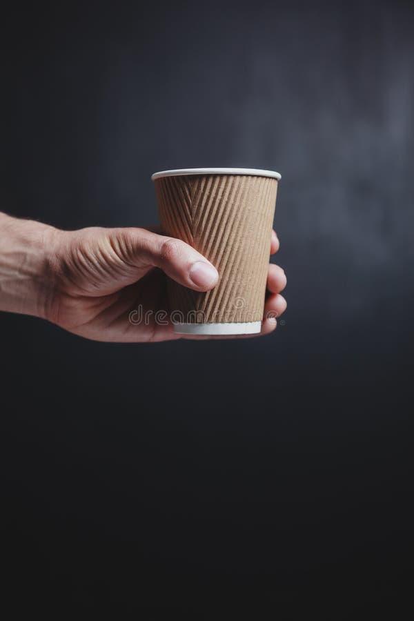 A mão do homem que guarda um copo de papel foto de stock